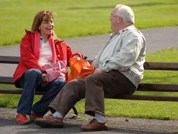 Rechtliche Betreuung: Eine Betreuerin unterhält sich mit ihrem Schützling auf einer Parkbank.